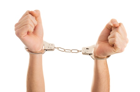 shackles: Close-up Hand Holding Handcuffs On White Background Stock Photo