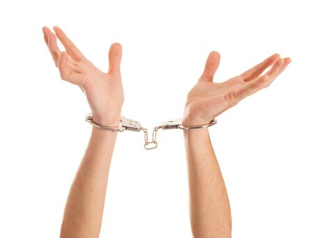 Close-up Hand Holding Handcuffs On White Background photo