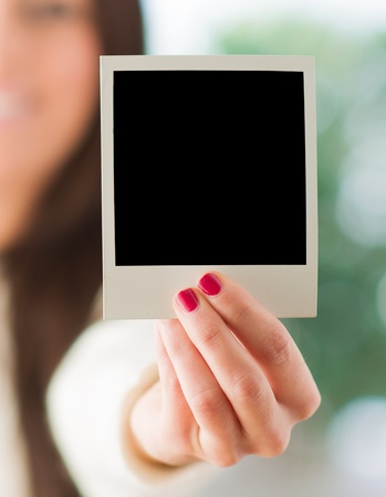 Close-up Of Womans Hand Holding Blank Instant Photo photo