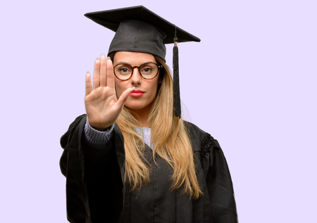Young woman university graduate student annoyed with bad attitude making stop sign with hand, saying no, expressing security, defense or restriction, maybe pushing Stock Photo