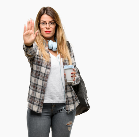 Young student woman with headphones and backpack annoyed with bad attitude making stop sign with hand, saying no, expressing security, defense or restriction, maybe pushing