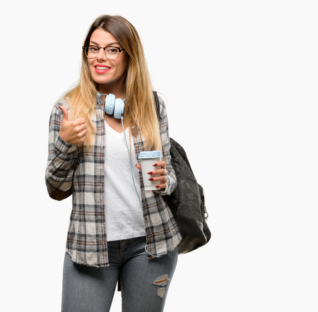 Young student woman with headphones and backpack smiling broadly showing thumbs up gesture to camera, expression of like and approval Stock Photo