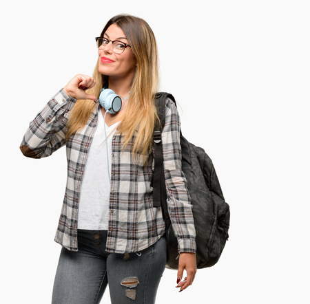 Young student woman with headphones and backpack proud, excited and arrogant, pointing with victory face