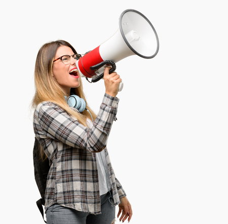 Young student woman with headphones and backpack communicates shouting loud holding a megaphone, expressing success and positive concept, idea for marketing or sales Stock Photo