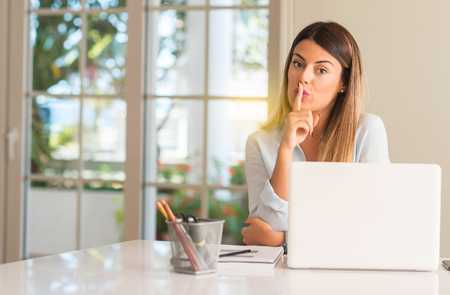 Student woman at table with laptop at home with index finger on lips, ask to be quiet. Silence and secret concept Stock Photo