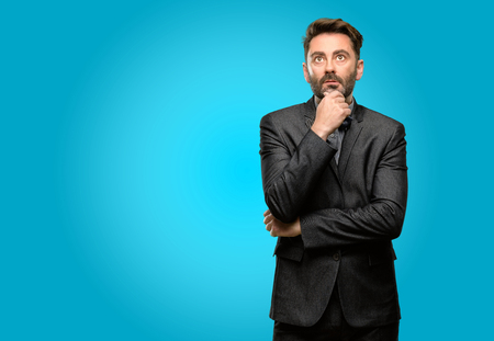 Middle age man, with beard and bow tie thinking and looking up expressing doubt and wonder