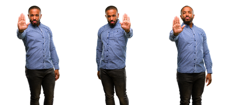 African american man with beard annoyed with bad attitude making stop sign with hand, saying no, expressing security, defense or restriction, maybe pushing Stock Photo