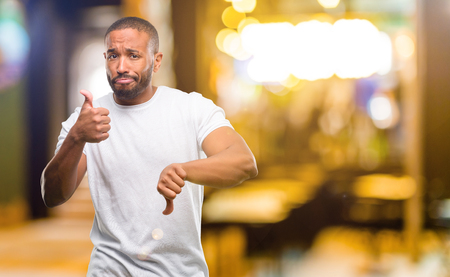 African american man with beard confused with thumbs up and down, trying to take a decision expressing doubt and frustration at night