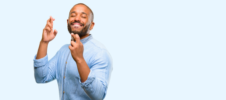 African american man with beard with crossed fingers asking for good luck isolated over blue background