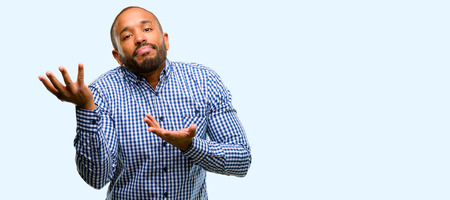 African american man with beard doubt expression, confuse and wonder concept, uncertain future isolated over blue background Banque d'images