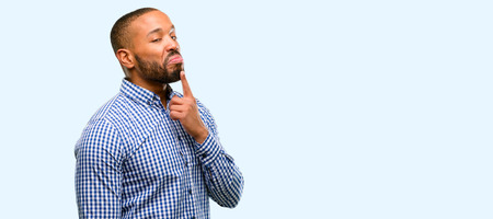 African american man with beard having skeptical and dissatisfied look expressing Distrust, skepticism and doubt isolated over blue background