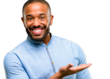 African american man with beard holding something in empty hand isolated over white background