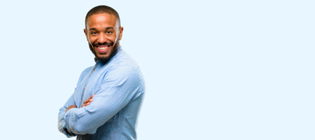 African american man with beard with crossed arms confident and happy with a big natural smile laughing isolated over blue background