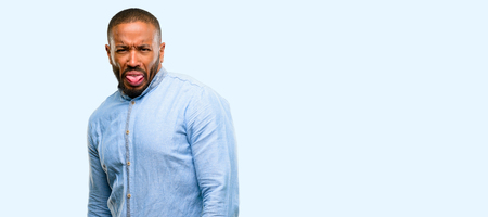 African american man with beard feeling disgusted with tongue out isolated over blue background