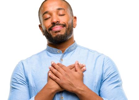 Homme afro-américain avec barbe avec les mains dans le coeur, exprimant l'amour et le concept de santé isolé sur fond blanc