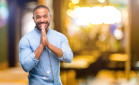 African american man with beard with hands together in praying gesture, expressing hope and please concept at night