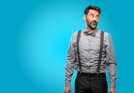 Middle age man, with beard and bow tie doubt expression, confuse and wonder concept, uncertain future Stock Photo