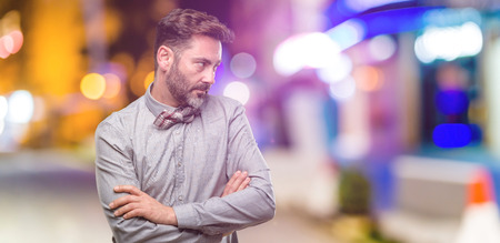 Middle age man, with beard and bow tie irritated and angry expressing negative emotion, annoyed with someone at night club