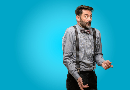 Middle age man, with beard and bow tie nervous and scared biting lips looking camera with impatient expression, pensive Stock Photo