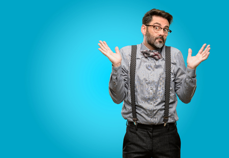 Middle age man, with beard and bow tie doubt expression, confuse and wonder concept, uncertain future shrugging shoulders Stock Photo