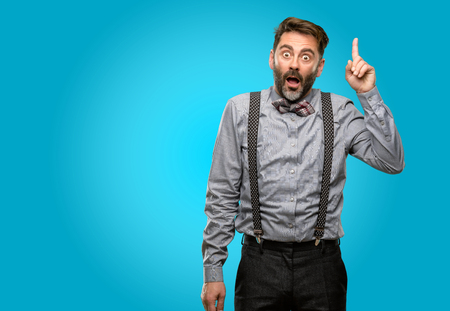 Middle age man, with beard and bow tie happy and surprised cheering expressing wow gesture pointing up