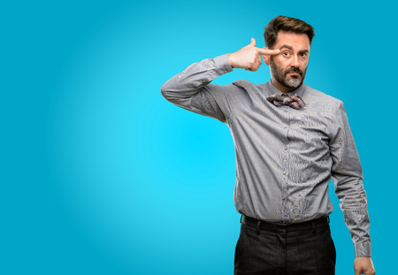 Middle age man, with beard and bow tie unhappy making suicide gesture, tired of everything. Shoots with hand imitating gun, upset Stock Photo