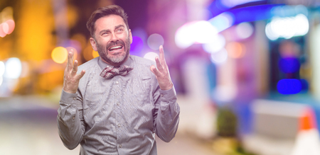 Middle age man, with beard and bow tie terrified and nervous expressing anxiety and panic gesture, overwhelmed at night club