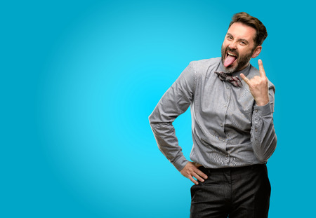 Middle age man, with beard and bow tie making rock symbol with hands, shouting and celebrating with tongue out