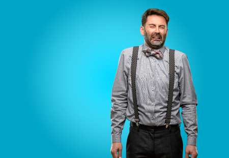 Middle age man, with beard and bow tie crying depressed full of sadness expressing sad emotion