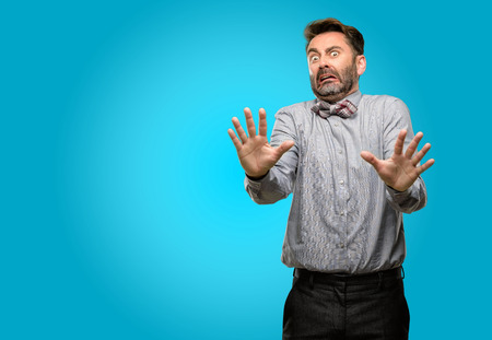 Middle age man, with beard and bow tie disgusted and angry, keeping hands in stop gesture, as a defense, shouting Stock Photo