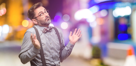 Middle age man, with beard and bow tie doubt expression, confuse and wonder concept, uncertain future at night club