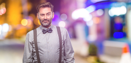 Middle age man, with beard and bow tie with sad and upset expression, unhappy at night club