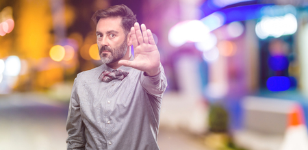 Middle age man, with beard and bow tie annoyed with bad attitude making stop sign with hand, saying no, expressing security, defense or restriction, maybe pushing at night club Stock Photo
