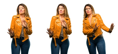Beautiful young woman disgusted and angry, keeping hands in stop gesture, as a defense, shouting over white background