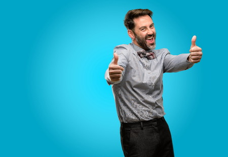 Middle age man, with beard and bow tie stand happy and positive with thumbs up approving with a big smile expressing okay gesture