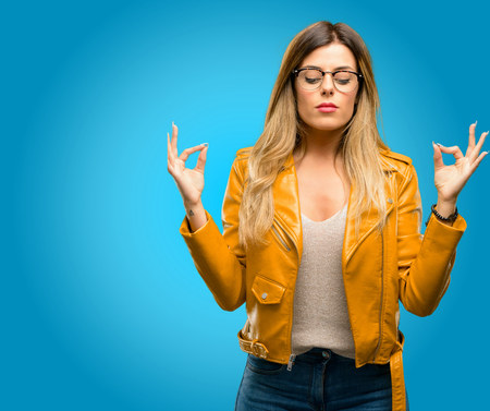 Beautiful young woman doing ok sign gesture with both hands expressing meditation and relaxation, blue background