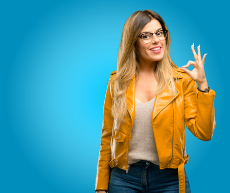 Beautiful young woman doing ok sign with hand, approve gesture, blue background Archivio Fotografico