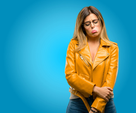 Beautiful young woman with sad and upset expression, unhappy, blue background