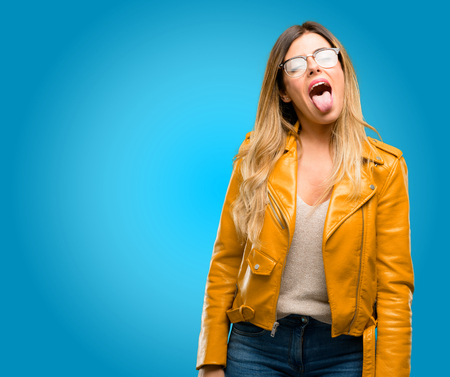 Beautiful young woman feeling disgusted with tongue out, blue background Stock Photo