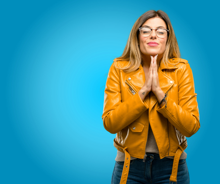 Beautiful young woman with hands together in praying gesture, expressing hope and please concept, blue background
