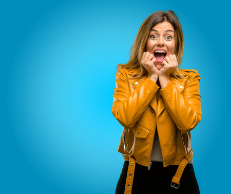 Beautiful young woman happy and surprised cheering expressing wow gesture, blue background