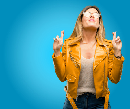 Beautiful young woman with crossed fingers asking for good luck, blue background Stock Photo