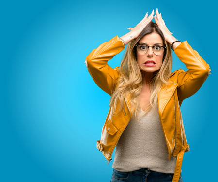 Beautiful young woman terrified and nervous expressing anxiety and panic gesture, overwhelmed, blue background