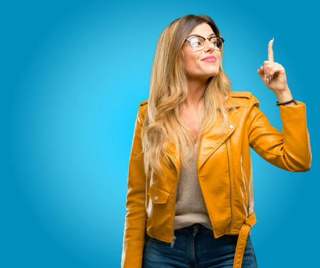 Beautiful young woman happy and surprised cheering expressing wow gesture pointing up, blue background Stock Photo
