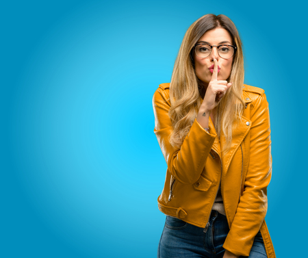 Beautiful young woman with index finger on lips, ask to be quiet. Silence and secret concept, blue background