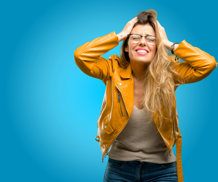 Beautiful young woman stressful keeping hands on head, terrified in panic, shouting, blue background Stock Photo