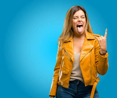 Beautiful young woman making rock symbol with hands, shouting and celebrating with tongue out, blue background