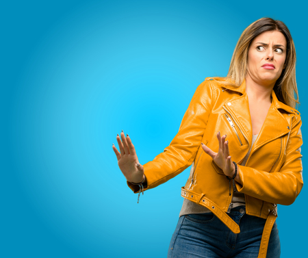 Beautiful young woman disgusted and angry, keeping hands in stop gesture, as a defense, shouting, blue background Stock Photo