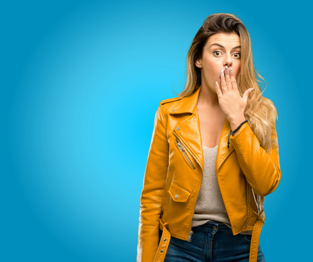 Beautiful young woman covers mouth in shock, looks shy, expressing silence and mistake concepts, scared, blue background
