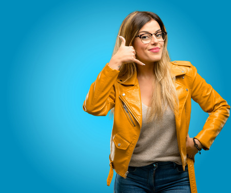 Beautiful young woman happy and excited making showing call me gesture with hand shaped like telephone, blue background Archivio Fotografico